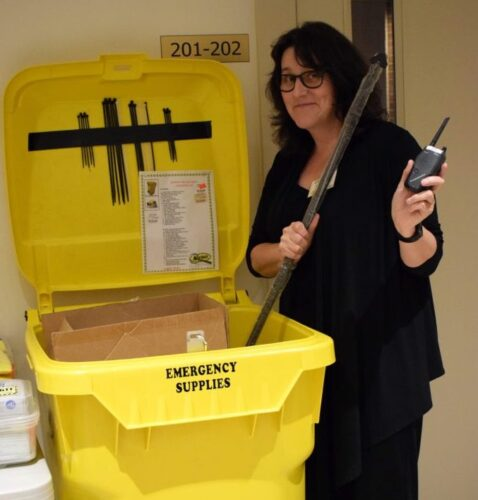 """A woman holding a walkie-talkie radio next to a large yellow wheelie bin labelled """"emergency supplies"""""""