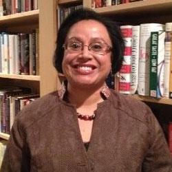 Dr. Atiya Mahmood stands beside a bookcase at SFU.