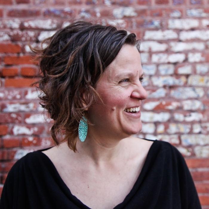 Michelle Hoar has a laugh against a brick wall.