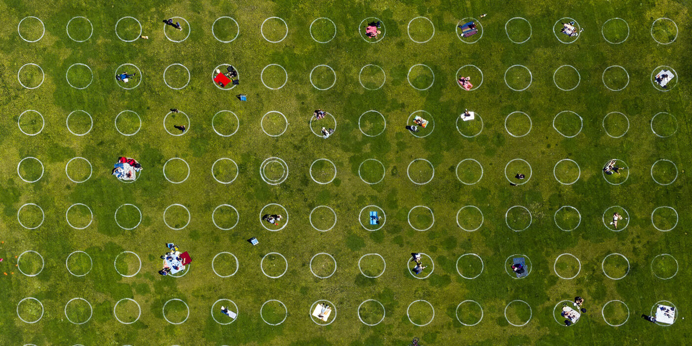 An aerial view of a field with white circles painted in a grid pattern. Some circles have small groups of people sitting in them. Circles are roughly 6 feet apart.